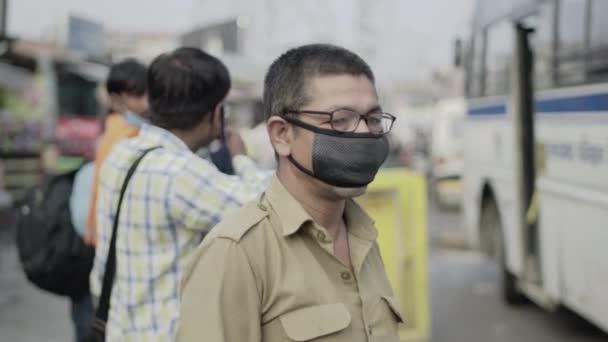 Egy maszkot viselő buszvezető utasokat hív az indiai Corona járvány idején..