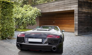 Luxury sports car in front of a garage