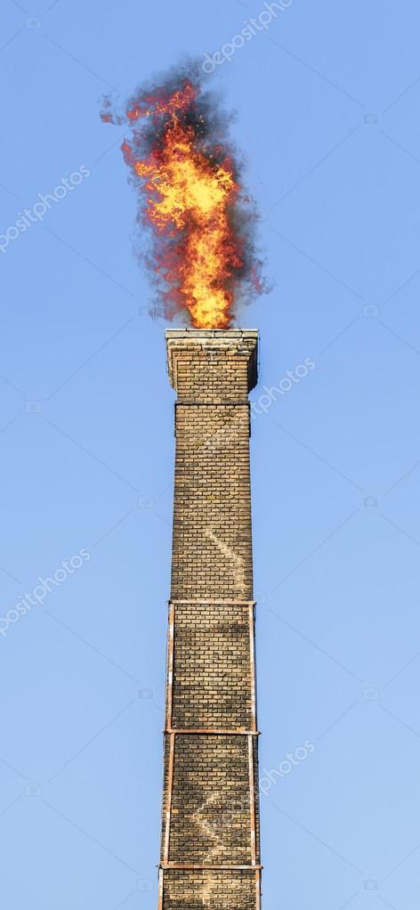 Old brick chimney on fire