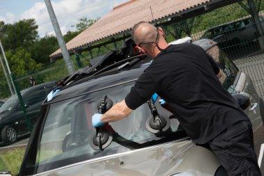 Glazier handling car windshield or windscreen made of glass outside