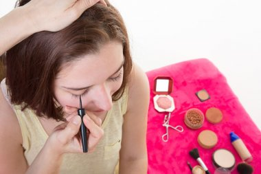 Make-up artist applying liquid eyeliner with brush, close up