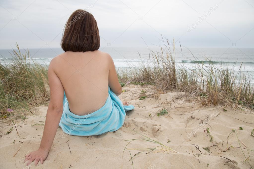 Mooie vrouw naakt zittend vanaf de achterkant op strand