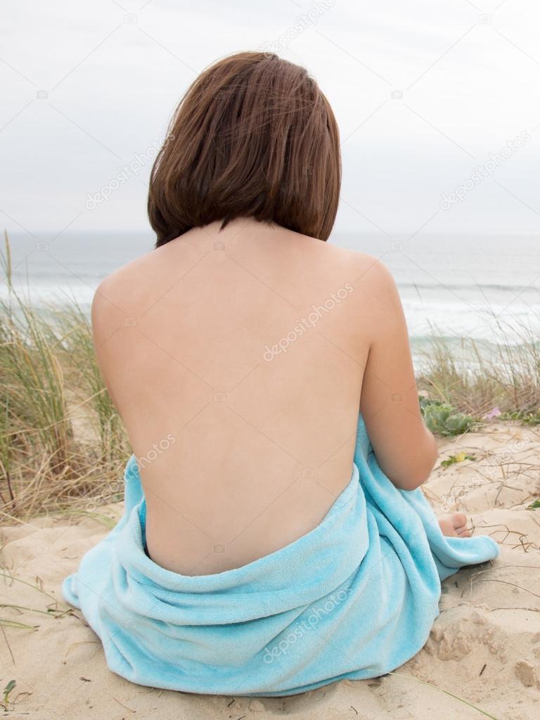 Naakt meisje op het zand zittend vanaf de achterkant op