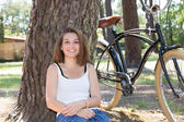 Young woman sitting in park while bicycle lying on foreground