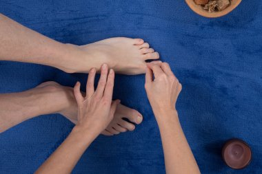 Close up of therapist's hands massaging male foot.