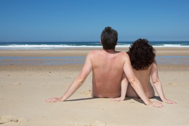 Relaxing nudist couple sitting on beach under deep blue sky