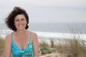 Žena stojící na pláži. Usmívající se dívka na kameru