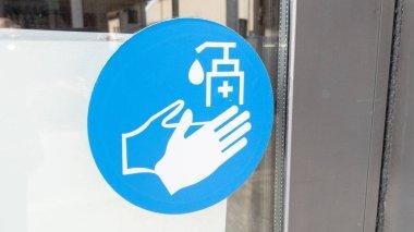 Liquid soap alcohol gel hand cleaning sign on door windows entrance shop