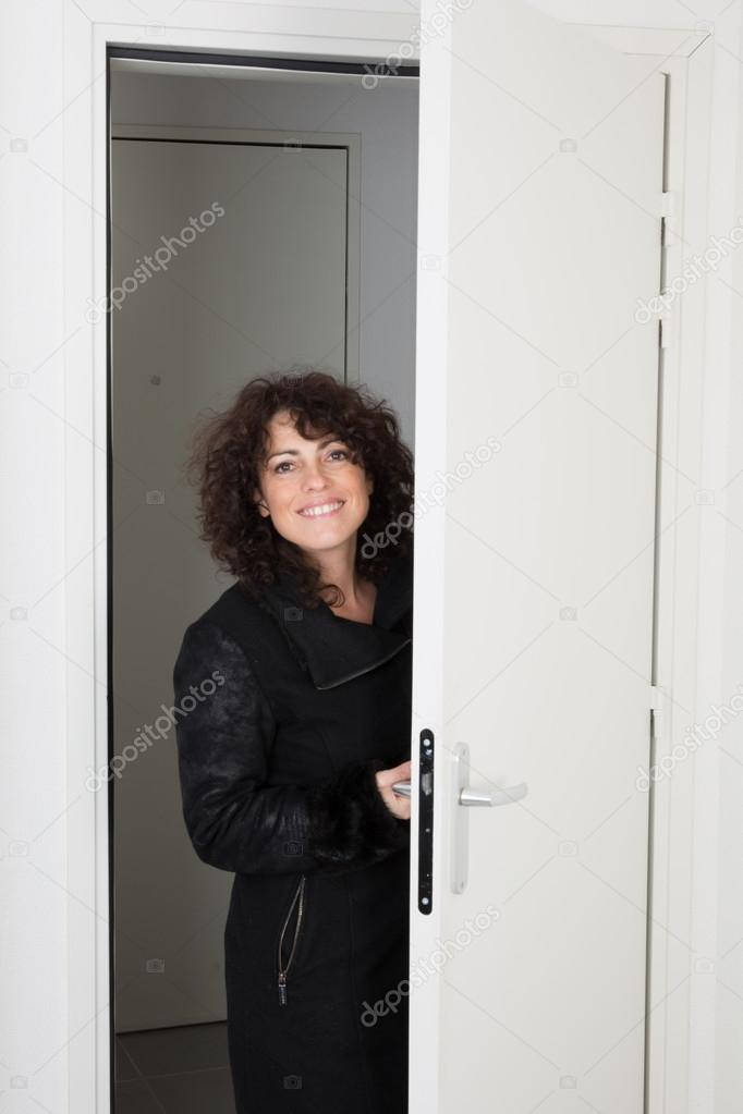 Woman Standing In Front Of Door Of Her House And Welcoming Guests To