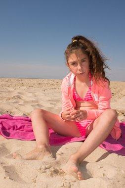 Little girl sitting  on the beach under blue sky