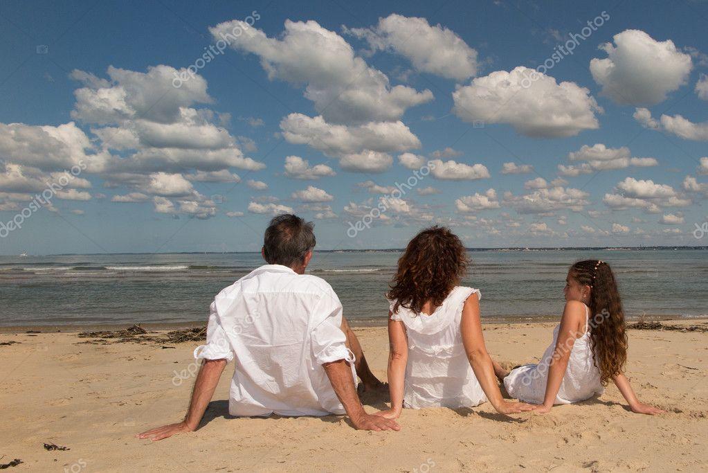 Nackt am Strand sitzen Familie. — Stockfoto © OceanProd
