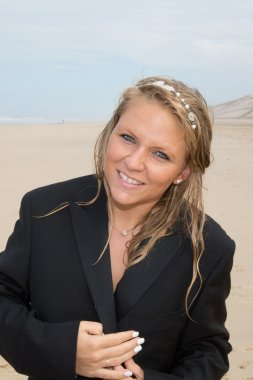 Blond  woman at the beach at summer time with a black jacket