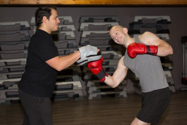 Two caucasian men exercising thai boxing at fitness center