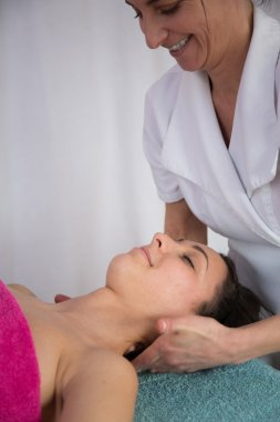 Woman getting neck massage at luxury spa centre