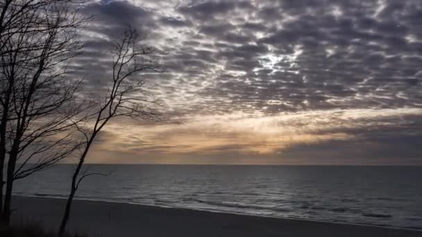 Timelapse movie of dramatic clouds at sunset above the sea