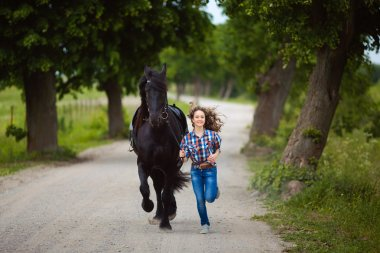 Young beautiful girl runs with the horse