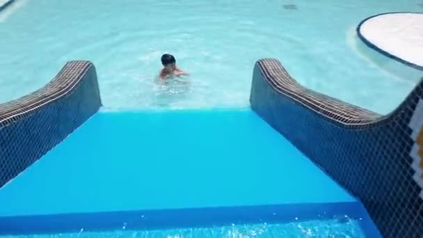 7 year old child playing on the slide in the pool on a summer day.