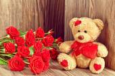 Valentines den. Milující medvídek s kyticí červených růží