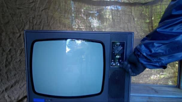 Egy védőruhás férfi csatornát vált egy régi retro TV-n.