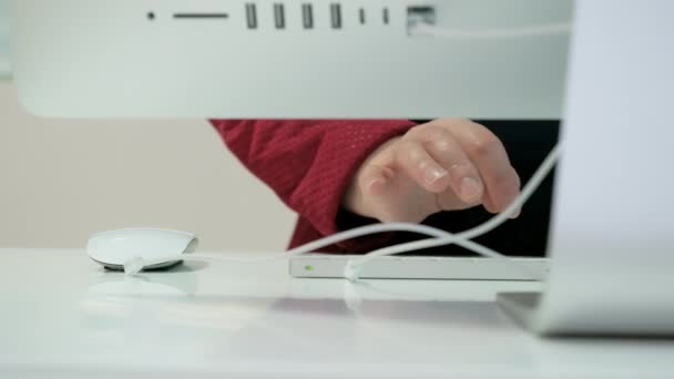 Woman works on big, white personal computer. Close up shot