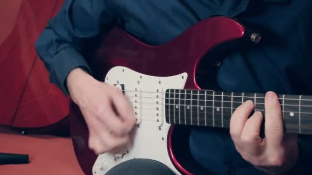 Ruce evropských mužů hrajících na elektrickou kytaru