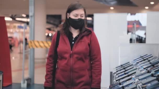 Dívka v masce a rukavice kupuje gadgets a zařízení v obchodě
