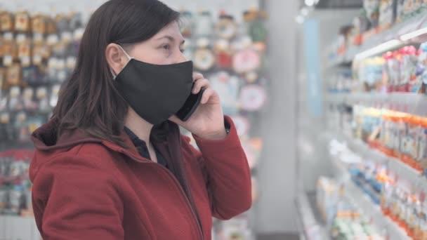 Európai nő maszkban, telefonnal, kiválaszt termékeket plázában