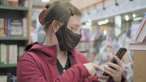 Egy nő szemüveget és maszkot visel a könyvesboltban, képeket készít a telefonján lévő könyvekről.
