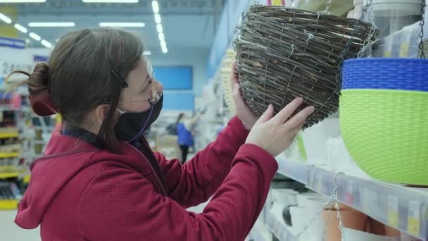 Woman in mask against virus buy wooden, wicker planters for flower pots in store