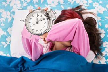 Young girl in bed covering eyes and holding alarm clock