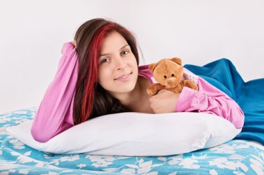 Young girl waking with her teddy bear