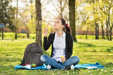 Student sitting on a meadow blowing soap bubbles