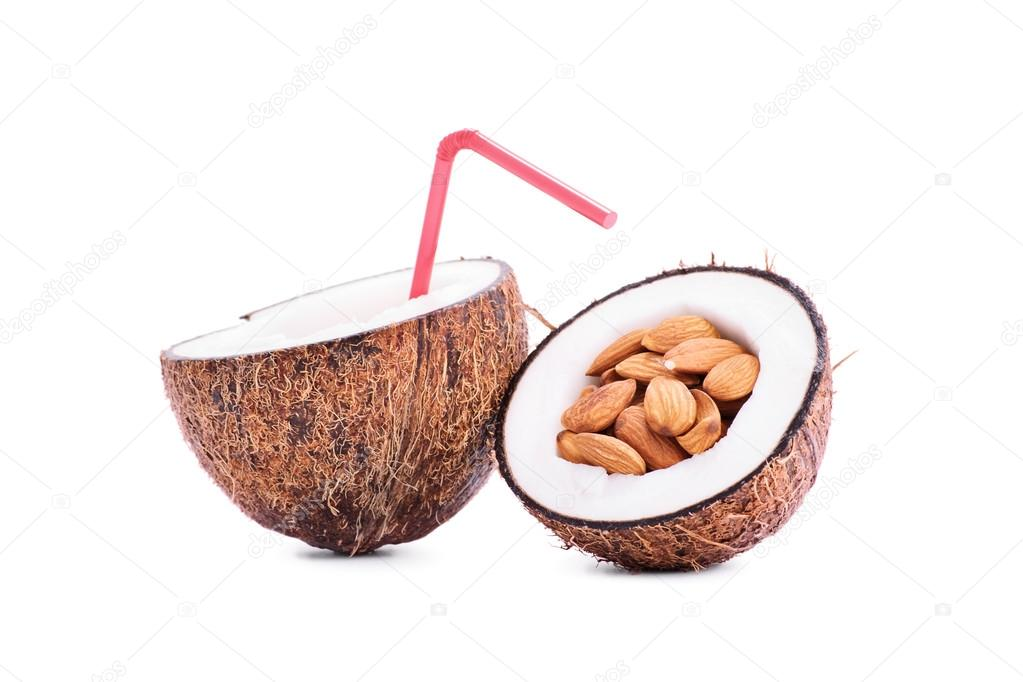 Sliced coconut filled with almonds and milk with a straw