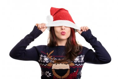 Portrait of a girl putting on a Santa's hat over her eyes