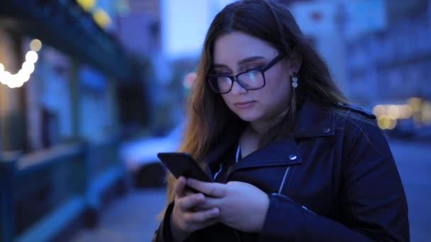 Frau plaudert im Smartphone vor dem Hintergrund der Abendstadt