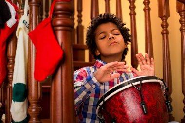 Enthusiastic darkskinned boy playing drum.