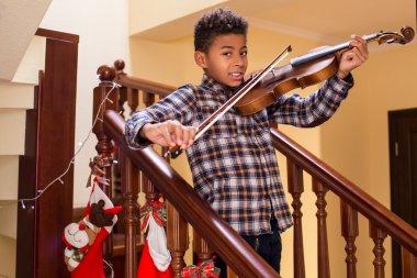Smiling afro kid plays violin.