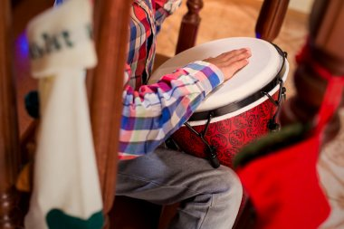 Mulatto child playing percussion drum.