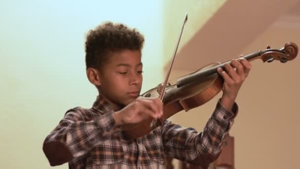 Smiling afro kid plays on violin.