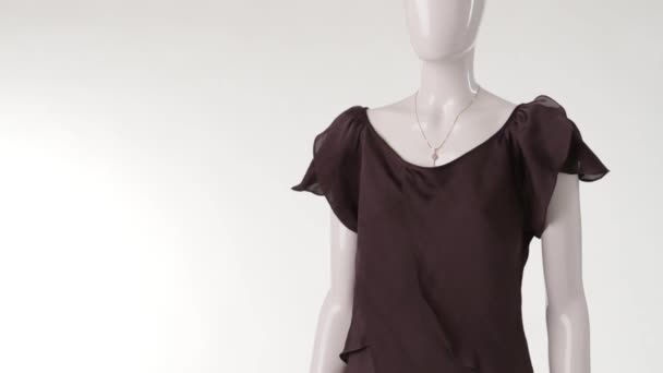 Thin brown blouse on mannequin.