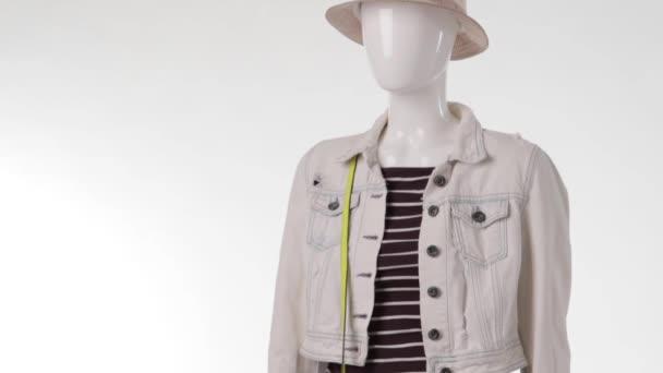 Female mannequin wearing denim jacket.