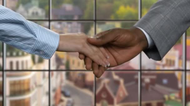 Černý muž potřásl rukou businesswomans.