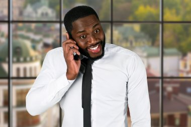Excited black businessman with cellphone.