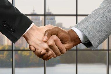 Businesspeople shake hands.