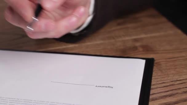 Businessmans hand signing paper.