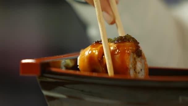 kéz evőpálcikával szusit eszik.