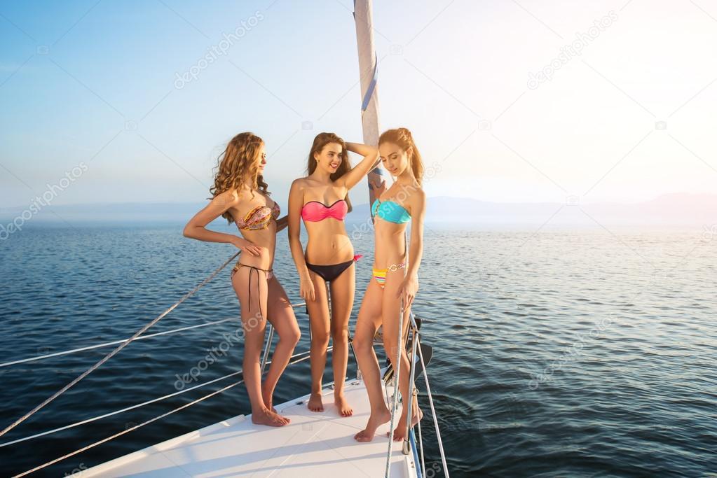 Girls standing on yacht deck.