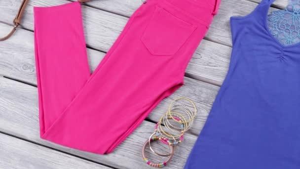 Modrý top a růžové kalhoty.