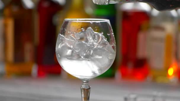 Flasche füllt Getränk ins Glas.