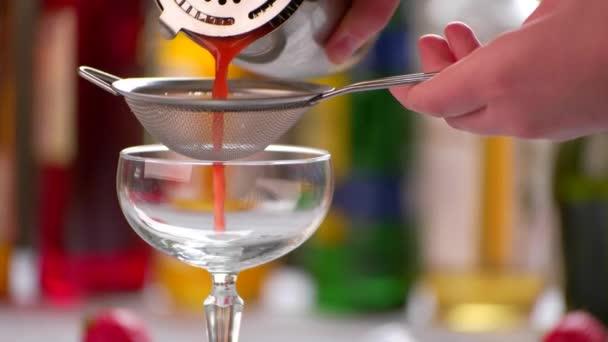 Rote cocktail gießt durch Sieb.